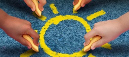 Community education and children learning and development concept with a group of hands representing ethnic groups of young people holding chalk cooperating together to draw a yellow sun shape as a metaphore for friendship.